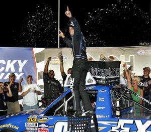 Photo -   James Buescher celebrates after winning the NASCAR Truck Series auto race at Kentucky Speedway, Thursday, June 28, 2012, in Sparta, Ky. (AP Photo/Garry Jones)