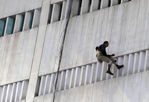 Photo - A man jumps from a building that caught on fire in Lahore, Pakistan, Thursday, May 9, 2013. The 13-storey government building caught fire and quickly intensified spreading to three floors of the tall building. (AP Photo/K.M. Chaudary)