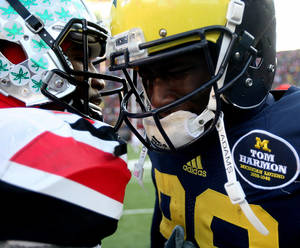 Photo - Michigans' Devin Gardner is comforted by Ohio States' Braxton Miller after Michigan's 42-41 loss in an NCAA college football game Saturday, Nov. 30, 2013 at Michigan Stadium in Ann Arbor, Mich. (AP Photo/Detroit Free Press,  Kirthmon F. Dozier) DETROIT NEWS OUT;  NO SALES, MANDATORY CREDIT