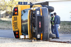 Photo - Emergency workers investigate an accident Tuesday involving a school bus and an automobile at the intersection of NW 89 and Classen Boulevard in Oklahoma City. photo BY PAUL HELLSTERN, THE OKLAHOMAN