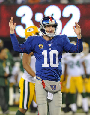 Photo -   New York Giants quarterback Eli Manning (10) signals a touchdown during the second half of an NFL football game, Sunday, Nov. 25, 2012 in East Rutherford, N.J. After further review Manning's pass to Hakeem Nicks was ruled a touchdown. (AP Photo/Bill Kostroun)