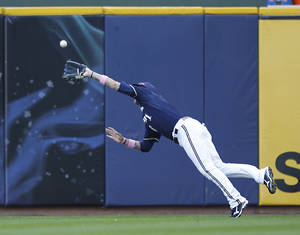 Photo -   Milwaukee Brewers' Corey Hart makes a diving catch on a ball hit by Chicago Cubs' Starlin Castro during the sixth inning of a baseball game on Sunday, May 13, 2012, in Milwaukee. (AP Photo/Jeffrey Phelps)