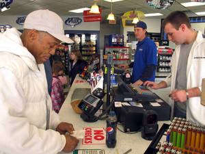 Photo -   Michael Arrington, left, buys a Powerball ticket from cashier Lee Heilig, right, on Friday, Nov. 23, 2012, at a DeliMart convenience store in Iowa City, Iowa. The jackpot had reached $325 million as of Friday. (AP Photo/Grant Schulte)