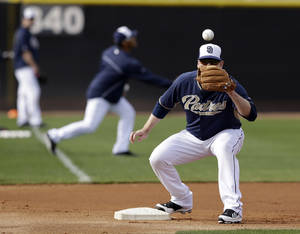 Photo - San Diego Padres third baseman Chase Headley waits for a throw in fielding drills during spring training baseball practice, Friday, Feb. 21, 2014, in Peoria, Ariz. (AP Photo/Tony Gutierrez)