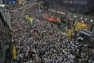 Photo - Tens of thousands of people fill in a street during a march at an annual protest in downtown Hong Kong Tuesday, July 1, 2014. Hong Kong residents marched through the streets of the former British colony to push for greater democracy in a rally fueled by anger over Beijing's recent warning that it holds the ultimate authority over the southern Chinese financial center. The protest comes days after nearly 800,000 residents voted in a mock referendum aimed at bolstering support for full democracy. (AP Photo/Vincent Yu)