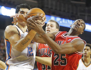 Photo - The Thunder's Steven Adams, left, and the Bulls' Marquis Teague battle for a rebound in the second quarter of a preseason game in Wichita, Kan. Claiming 69.4 percent of contested rebounds, Adams is the best in the league among players who see 15 minutes of action or more. AP Photo