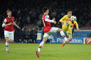 Photo - Napoli's Jose Callejon, right, scores during a Champions League, group F, soccer match between Napoli and Arsenal, at the Naples San Paolo stadium, Italy, Wednesday, Dec. 11, 2013. Ten-man Arsenal advanced to the Champions League knockout phase for the 14th consecutive year despite a 2-0 loss Wednesday at Napoli, which was eliminated. Gonzalo Higuain scored in the 73rd minute but the San Paolo stadium was soon silenced when word arrived that Borussia Dortmund had scored a late goal in a 2-1 win at Marseille to win Group F. (AP Photo/Gennaro Giorgio)