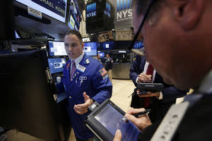 Photo - Specialist Jason Hardzewicz, left, works at his post on the floor of the New York Stock Exchange Tuesday, July 8, 2014. U.S. stocks are opening lower for a second day in a row as investors position themselves for corporate earnings reports. (AP Photo/Richard Drew)