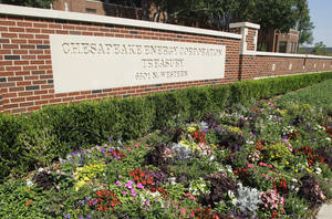 photo - Flowers grow in front of a sign at the Chesapeake campus in Oklahoma City.  AP Archives Photo