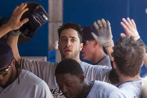 Photo - Milwaukee Brewers Ryan Braun celebrates in the dugout after scoring on a sacrifice fly by Jonathan Lucroy during third inning interleague baseball action against the Toronto Blue Jays in Toronto on Wednesday July 2 , 2014. (AP Photo/The Canadian Press, Chris Young)