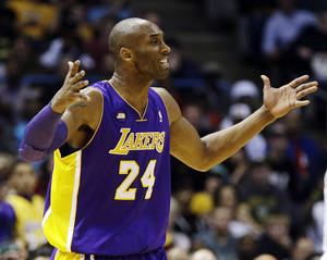 Photo - Los Angeles Lakers' Kobe Bryant argues a call against the Milwaukee Bucks during the second half of an NBA basketball game, Thursday, March 28, 2013, in Milwaukee. The Bucks won 113-103.(AP Photo/Jeffrey Phelps)