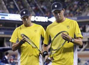 Photo - Mike Bryan, right, and his twin brother Bob Bryan check their racquets during their match against Colin Fleming and Jonathan Marray, both of Britain, during the men's quarterfinal round of the 2013 U.S. Open tennis tournament, Monday, Sept. 2, 2013, in New York. (AP Photo/Charles Krupa)