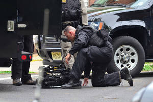 Photo - A state police swat team member readies a robot to enter a home where a man had barricaded himself on Friday, May 10, 2013 in Trenton, N.J.  The standoff with an armed man who police said took multiple hostages entered its second day Saturday as authorities worked to negotiate his surrender and his captives' safe release. The man, whose identity has not been released, was holed up in a brick house in South Trenton more than 18 hours after the standoff began Friday afternoon, authorities said.   (AP Photo/The Trentonian, Scott Ketterer)  TRENTON TIMES OUT; PHILLY METRO OUT