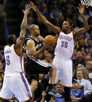 Photo - San Antonio's Tony Parker (9) moves between Oklahoma City's Kevin Durant (35) and Kendrick Perkins (5) during an NBA basketball game between the Oklahoma City Thunder and the San Antonio Spurs at Chesapeake Energy Arena in Oklahoma City, Wednesday, Nov. 27, 2013. Photo by Nate Billings, The Oklahoman