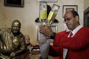 Photo - FILE - This July 21, 2012 file photo shows bartender Alejandro Bolivar preparing a daiquiri at El Floridita tavern in Old Havana, Cuba, to honor the 195th anniversary of the bar and the anniversary of the birth of its most famous frequent customer, novelist Ernest Hemingway, of whom a life-sized sculpture sits barside. Legend has it that Hemingway once downed 13 doubles in one sitting. There are sites connected to Hemingway in many different locales including Florida, Cuba, Arkansas, Idaho and Illinois.  (AP Photo/Franklin Reyes, File)