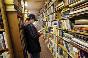 Photo - Left: Zach Olson, 13, a student at Summit Middle School in Edmond, looks through books at the Aladdin Book Shoppe in the Mayfair Village shopping center at NW 50 and N May Avenue.