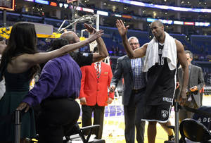 Photo - Brooklyn Nets center Jason Collins, right, is congratulated by fans after they defeated the Los Angeles Lakers in an NBA basketball game, Sunday, Feb. 23, 2014, in Los Angeles. Brooklyn won 108-102. (AP Photo/Mark J. Terrill)