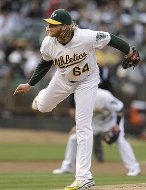 Photo - Oakland Athletics' A.J. Griffin follows through on a pitch to the Toronto Blue Jays in the first inning of a baseball game Monday, July 29, 2013, in Oakland, Calif. (AP Photo/Ben Margot)