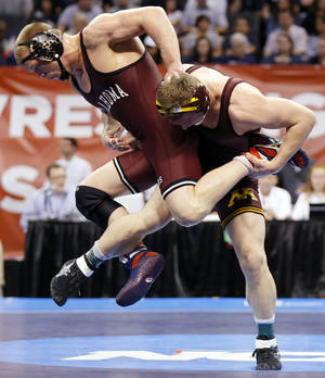 Photo - OU's Andrew Howe, left, wrestles Minnesota's Logan Storley in a 174-pound semifinal during the 2014 NCAA Div. I Wrestling Championships at Chesapeake Energy Arena in Oklahoma City, Friday, March 21, 2014. Howe won and advanced to the championship. Photo by Nate Billings, The Oklahoman
