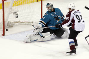 Photo - Colorado Avalanche's Gabriel Landeskog, right, scores past San Jose Sharks goalie Antti Niemi during the first period of an NHL hockey game, Monday, Dec. 23, 2013, in San Jose, Calif. (AP Photo/George Nikitin)