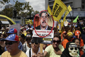 "Photo - A protester holds up a picture of Venezuela's Vice President Nicolas Maduro that reads in Spanish ""Big red package, plus inflation"" during an opposition demonstration against of the devaluation of the currency in Caracas, Venezuela, Saturday, Feb. 23, 2013. Venezuela's government announced on Friday, Feb. 8 that it is devaluing the country's currency, a long-anticipated change expected to push up prices in the heavily import-reliant economy. Venezuela's government has had strict currency exchange controls since 2003 and maintains a fixed, government-set exchange rate. While those controls have restricted the amounts of dollars available at the official rate, an illegal black market has flourished and the value of the bolivar has recently been eroding.  (AP Photo/Ariana Cubillos)"