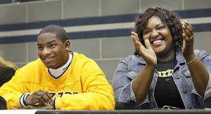Photo - Edmond North's Xavier Smith and his mom, Judy, celebrate after Xavier signed with Missouri on Wednesday. PHOTO BY DAVID MCDANIEL, THE OKLAHOMAN