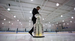 photo - Mike Bolt, keeper of the Stanley Cup, takes it off the ice after members of the Vancouver Angels novice C1 minor hockey team were surprised with it before their youth practice  Friday, Dec. 7, 2012, in Vancouver, British Columbia. Five minor hockey teams in Canada were randomly chosen to receive a surprise appearance by the Stanley Cup as part of the Scotiabank Community Hockey Sponsorship Program. The NHL lockout is in its 82nd day.  (AP Photo/The Canadian Press, Darryl Dyck)