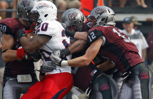 Photo -   Liberty running back Aldreakis Allen (20) is stopped by a host of Montana defenders during an NCAA college football game in Missoula, Mont., on Saturday, Sept. 15, 2012. (AP Photo/Michael Albans)