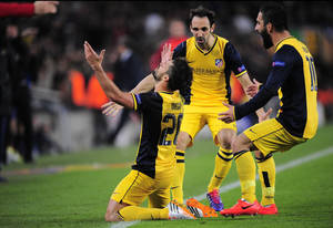 Photo - Atletico's Diego, left, celebrates with Diego Godin, centre and Arda Turan after scoring during a first leg quarterfinal Champions League soccer match between Barcelona and Atletico Madrid at the Camp Nou stadium in Barcelona, Spain, Tuesday April 1, 2014. (AP Photo/Manu Fernandez)