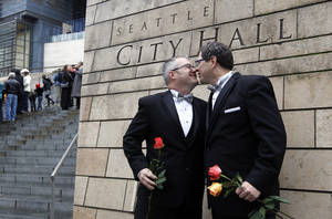 photo - Terry Gilbert, left, kisses his husband Paul Beppler after wedding at Seattle City Hall, becoming among the first gay couples to legally wed in the state, Sunday, Dec. 9, 2012, in Seattle. Gov. Chris Gregoire signed a voter-approved law legalizing gay marriage Dec. 5 and weddings for gay and lesbian couples began in Washington on Sunday, following the three-day waiting period after marriage licenses were issued earlier in the week. (AP Photo/Elaine Thompson)