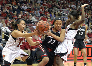 Photo - Cincinnati's Bianca Quisenberry, center, grabs a rebound away from the defense of Louisville's Shoni Schimmel, left, and Monny Niamke during the first half of an NCAA college basketball game Saturday Jan. 4, 2014, in Louisville, Ky. (AP Photo/Timothy D. Easley)
