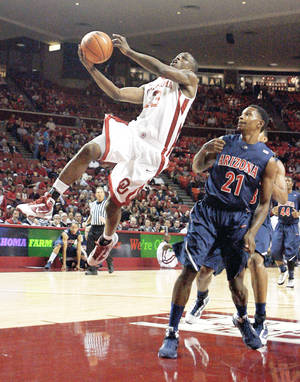 Photo - OU's Willie Warren, left, shoots a layup in front of Arizona's Kyle Fogg during action earlier this month. Warren is capable  of carrying  the Sooners this season. Photo by Sarah Phipps, The Oklahoman