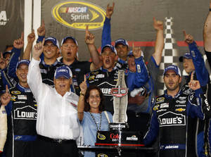 Photo - FILE - In this July 6, 2013, file photo, driver Jimmie Johnson, far right, celebrates with his crew and car owner Rick Hendrick, left, after winning the NASCAR Sprint Cup auto race at Daytona International Speedway in Daytona Beach, Fla. Hendrick watched victory slip away for two of his drivers at Auto Club Speedway. Johnson was leading in the closing laps until a tire failure sent him to pit road and cost him his first win of the season. His misfortune appeared to be Hendrick Motorsports teammate Jeff Gordon's gain, though, as Gordon inherited the lead from Johnson. (AP Photo/Reinhold Matay, File)