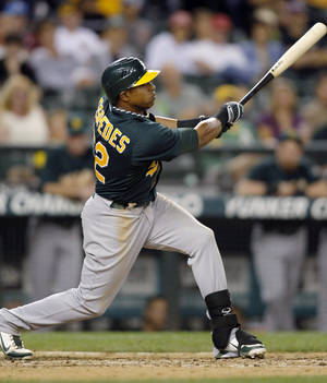 photo -   Oakland Athletics&#039; Yoenis Cespedes hits a sacrifice fly to score a run against the Seattle Mariners during the ninth inning of a baseball game in Seattle on Saturday, Sept. 8, 2012. The Athletics won 6-1. (AP Photo/John Froschauer)  