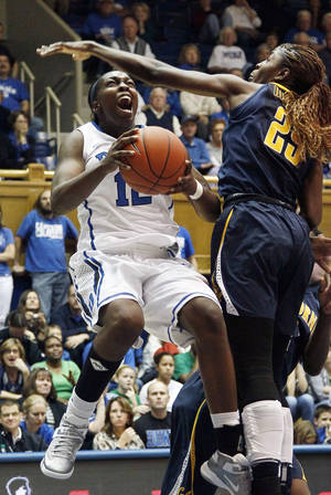 Photo - Duke's Chelsea Gray (12) drives to the basket against California's Gennifer Brandon (25) during the second half of an NCAA women's college basketball game in Durham, N.C., Sunday, Dec. 2, 2012. Duke won 77-63. (AP Photo/Gerry Broome)
