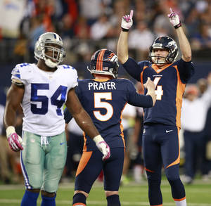Photo - Denver Broncos punter Britton Colquitt (4) and Matt Prater (5) celebrates their winning field goal in front of Dallas Cowboys outside linebacker Bruce Carter (54) during the second half of an NFL football game Sunday, Oct. 6, 2013, in Arlington, Texas. The Broncos won 51-48. (AP Photo/Waco Tribune Herald, Jose Yau) ORG XMIT: TXWAC123