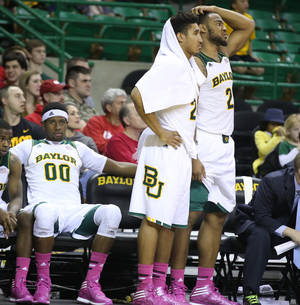 Photo - Baylor guard/forward Ish Wainright, center, along with forward Rico Gathers (2) and Royce O'Neale, left, watch from the bench in the second half of an NCAA college basketball game against Texas, Saturday, Jan. 25, 2014, in Waco, Texas. (AP Photo/Waco Tribune Herald, Rod Aydelotte)