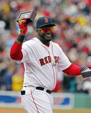Photo - Boston Red Sox's David Ortiz holds up his World Series ring during pre-game ceremonies before a baseball game between the Red Sox and the Milwaukee Brewers on opening day at Fenway Park in Boston, Friday, April 4, 2014. (AP Photo/Michael Dwyer)