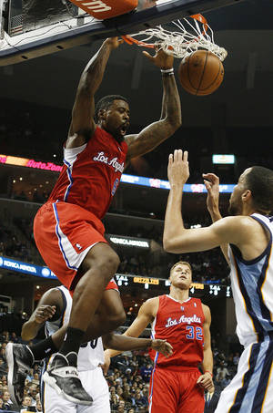 Photo - Los Angeles Clippers center DeAndre Jordan (6) dunks the ball over Memphis Grizzlies forward Tayshaun Prince, right, in the first half of an NBA basketball game on Thursday, Dec. 5, 2013, in Memphis, Tenn. (AP Photo/Lance Murphey)