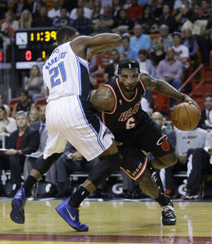 Photo - Miami Heat small forward LeBron James (6) drives around Orlando Magic small forward Maurice Harkless (21) during the first half of an NBA basketball game in Miami, Saturday, March 1, 2014. (AP Photo/Alan Diaz)
