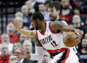 photo - Portland Trail Blazers forward LaMarcus Aldridge, right, drives past Memphis Grizzlies center Marc Gasol, of Spain, during the first quarter of an NBA basketball game in Portland, Ore., Tuesday, March 12, 2013. (AP Photo/Don Ryan)