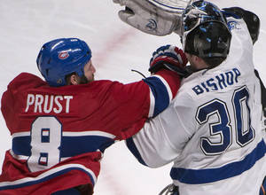 Photo - Tampa Bay Lightning goalie Ben Bishop gets a punch to the face during a break in play by Montreal Canadiens' Brandon Prust  during the second period of an NHL game in Montreal, Saturday, Feb. 1, 2014. (AP Photo/The Canadian Press, Peter McCabe)