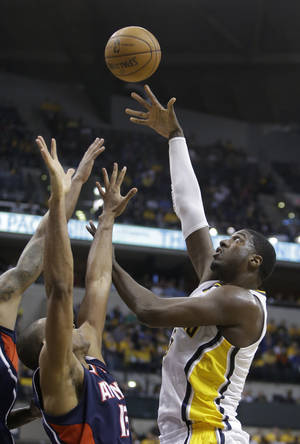 Photo - Indiana Pacers' Roy Hibbert shoots against Atlanta Hawks' Al Horford during the second half of Game 1 in the first round of the NBA basketball playoffs on Sunday, April 21, 2013, in Indianapolis. Indiana defeated Atlanta 107-90. (AP Photo/Darron Cummings)