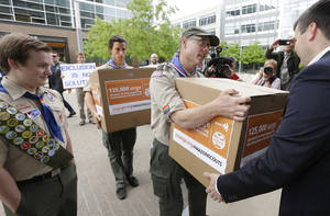 Photo - Geoffrey McGrath, center, a gay Boy Scout troop leader and Eagle Scout from Seattle, who had his membership in the Scouts revoked by the organization earlier this year, hands Amazon.com security worker Matt Oien, right, a box, Wednesday, May 21, 2014, at Amazon headquarters in Seattle that was one of four containing signatures and comments on a petition to Amazon.com urging the company to stop donating money to the Boy Scouts due to the organization's policy of excluding openly gay adults from leadership positions, despite recently accepting gay youth as scouts. The petition was started by Pascal Tessier, 17, left, a gay Eagle Scout from Kensington, Md. (AP Photo/Ted S. Warren)