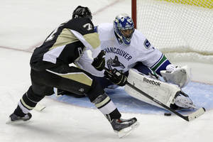 Photo - Pittsburgh Penguins' Evgeni Malkin (71) gets the game-winning goal past Vancouver Canucks goalie Roberto Luongo (1) in an overtime shootout during an NHL hockey game in Pittsburgh Saturday, Oct. 19, 2013. The Penguins won  4-3. (AP Photo/Gene J. Puskar)
