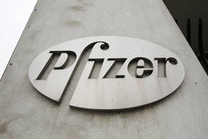 Photo - In this May 4, 2014 photo, the Pfizer logo is displayed on the exterior of a former Pfizer factory  in the Brooklyn borough of New York. Pfizer says it does not intend to make a takeover offer for British drugmaker AstraZeneca. The Monday, May 26, 2014 announcement comes a week after AstraZeneca's board rejected a proposed $119 billion buyout offer from Pfizer, the world's second-biggest drugmaker by revenue. (AP Photo/Mark Lennihan, File)