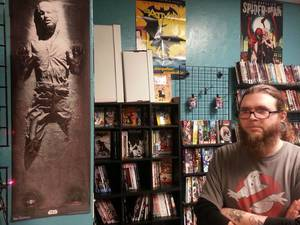 Photo - Bryan O'Quinn of Empire Strikes Books stands near a poster of a frozen Han Solo in his shop at 600 NW 23, suite 103.   Photo by Matthew Price, The Oklahoman.   <strong></strong>