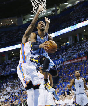 Photo - Memphis Grizzlies guard Mike Conley (11) goes up for a shot in front of Oklahoma City Thunder forward Serge Ibaka (9) in the second quarter of Game 2 of an opening-round NBA basketball playoff series in Oklahoma City, Monday, April 21, 2014. (AP Photo/Sue Ogrocki)