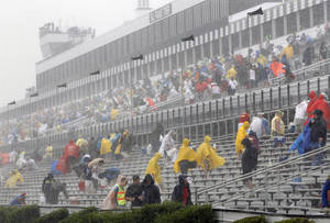 photo -   Fans leave the stands after the start of the NASCAR Sprint Cup Series auto race was postponed due to rain on Sunday, Aug. 5, 2012, at Pocono Raceway in Long Pond, Pa. (AP Photo/Mel Evans)