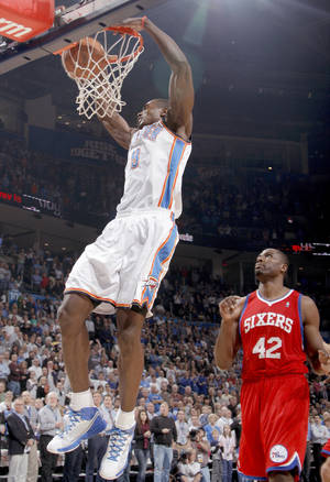 Photo - The Thunder's Serge Ibaka dunks over Philadelphia's Elton Brand on Wednesday. Photo by Bryan Terry, The Oklahoman